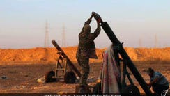 Islamic State militants prepare to fire a mortar to