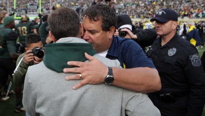 Michigan State football coach Mark Dantonio and Michigan coach Brady Hoke, right, hug at midfield after a game Oct. 15, 2011.