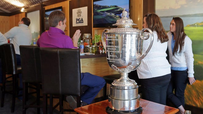 People enjoy the hospitality chalet on display at Whistling Straits on Tuesday, where the Wanamaker trophy was on display.
