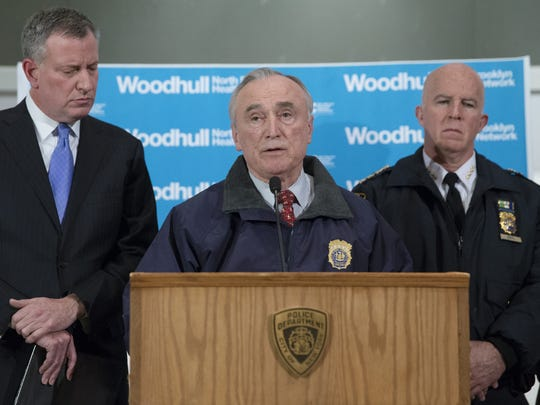 New York Police Department Commissioner Bill Bratton speaks alongside Mayor Bill de Blasio, left, and NYPD's Chief of Department James O'Neill, right, during a news conference at Woodhull Medical Center, Saturday, Dec. 20, 2014, in New York.  An armed man walked up to two New York Police Department officers sitting inside a patrol car and opened fire Saturday afternoon, killing one and critically wounding a second before running into a nearby subway station and committing suicide, police said. (AP Photo/John Minchillo)