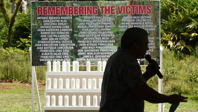 This Aug. 8 file photo shows a sign with the names of the 45 victims of the Chagui'an massacre, with Gov. Eddie Calvo speaking during a memorial service in the forefront.