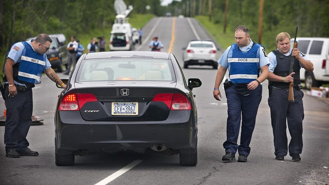 New York State corrections officers check vehicles along State Route 30 at the intersection with Travers Rd. in the town of Malone, N.Y. on Saturday, June 27, 2015 as the search for escaped prisoner David Sweat continues. (Jason Hunter/Watertown Daily Times via AP)