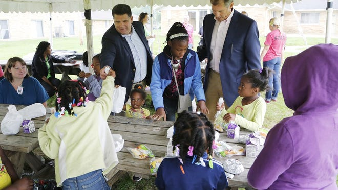 Mayors Tony Roswarski and John Dennis meet with youngsters during Food Finders Food Bank's summer feeding program Wednesday, July 8, 2015, at Claystone at the Crossing Apartments, 548 Westchester Lane, Lafayette.
