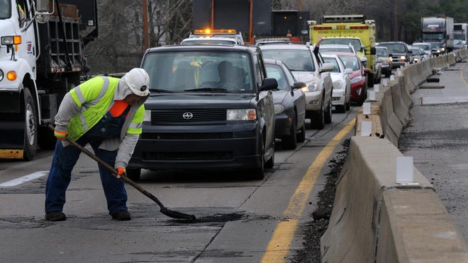 Ken Song repairs a pothole on Interstate 440. The Tennessee Department of Transportation has bolstered its safety policies since 2010. John Partipilo / The Tennessean