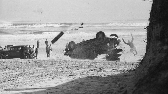In this March 2, 1936, file photo, driver Bobby Sall, of Patterson, N.J., leaps from his overturned race car during a test run for a 250-mile stock car auto race in Daytona Beach, Fla.