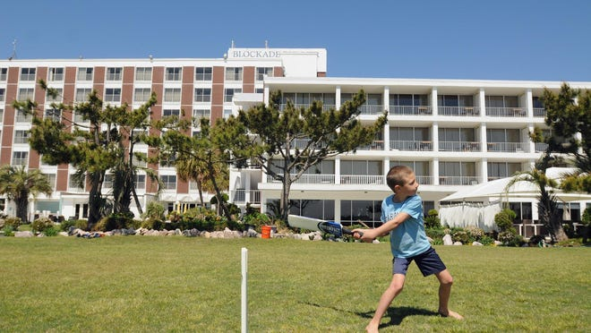 """Stephen """"Tractor"""" Gerbracht, 8, plays a game of cricket with his family from Brooktondale, N.Y., on the lawn of the Blockade Runner Beach Resort in Wrightsville Beach on Wednesday, April 16, 2014."""