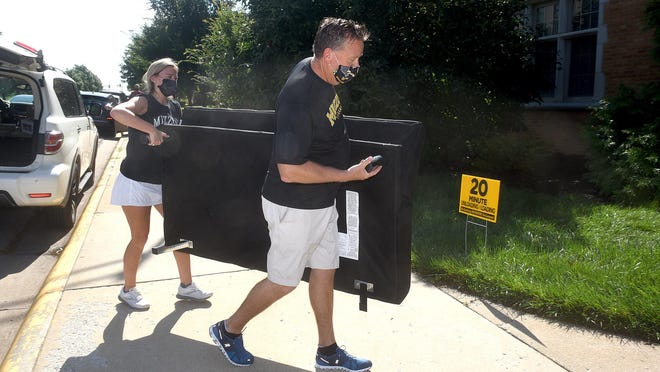 Brian Sullivan of St. Louis helps his daughter, Bridget Sullivan, a freshman, move a futon into her dorm room in Johnston Hall at MU in the beginning of the fall semester. Returning undergrads living on campus will be required to be tested for COVID-19 before the spring semester's start.