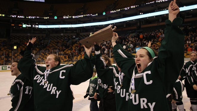 Duxbury High School co-captains Elizabeth Collins, right, and Rachel Myette, along with Zoe Griffin, far left, celebrate their victory in the Div. 1 state girls hockey championship on Sunday, March 16, 2014 at TD Garden in Boston.