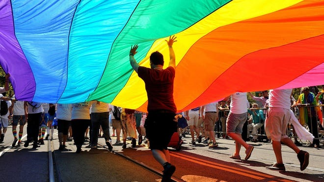 Parade participants march down Market Street carrying the rainbow flag during the annual Gay Pride parade in San Francisco on June 30, 2013.