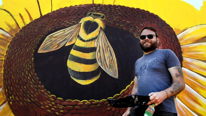 Artist Allan Potter stands in front of a portion of the mural he is painting on the side of the building located at 117 E. Virginia Ave. in downtown Bessemer City.