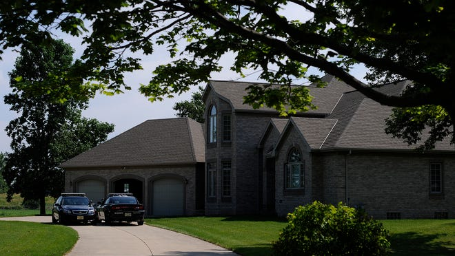 Two squad cars from the Brown County Sheriff's Department sit outside the home where a home invasion occurred July 11, 2013 on Van Lake Court in Bellevue.
