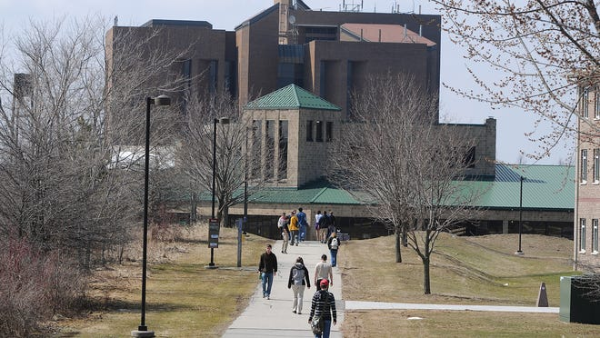 UWGB students walk along a sidewalk that connects the University Union and several dormitories.