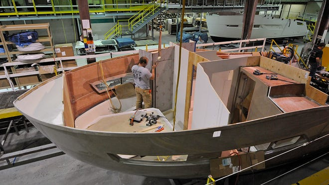 Bill Beschta works on installing cabinets to the owners cabin inside a Carver C37 yacht at Marquis Yachts in Pulaski on Oct. 24, 2014.