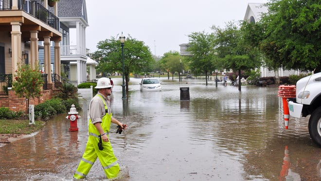 Gulf Power line crews restore power in Pensacola after historic flooding in April 2014.