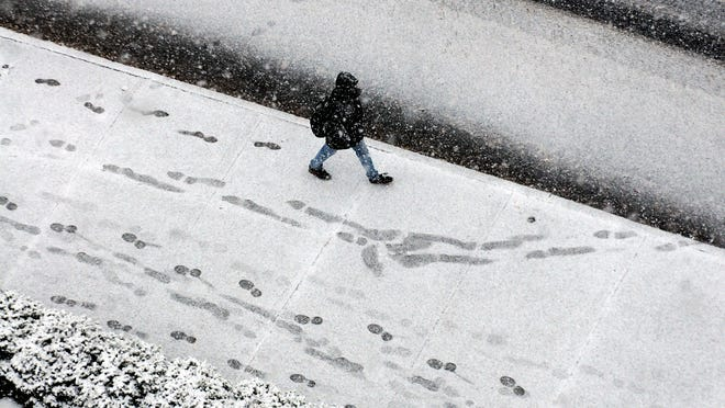 A pedestrain adds his tracks to the snow while walking along Civic Center Plaza Wednesday in Poughkeepsie.