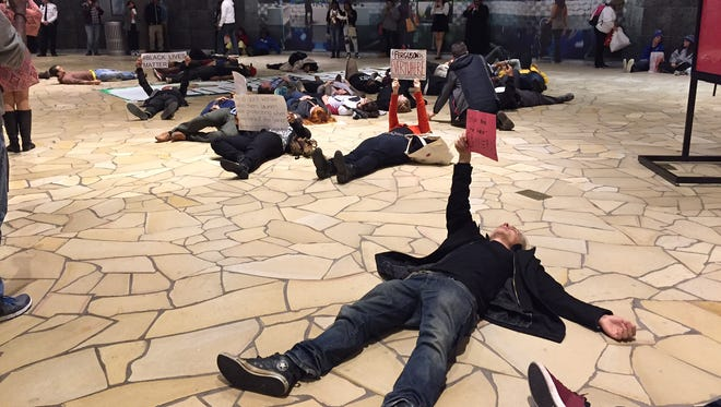 """About a dozen protesters stage a """"die-in"""" at Opry Mills mall on Saturday evening."""