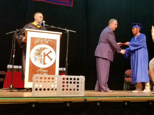Tyler Adams receives his Roy C. Ketcham High School diploma from his stepfather, Darryl Sullivan, as Ketcham principal Dave Seipp stands at a podium on Saturday at the Mid-Hudson Civic Center.