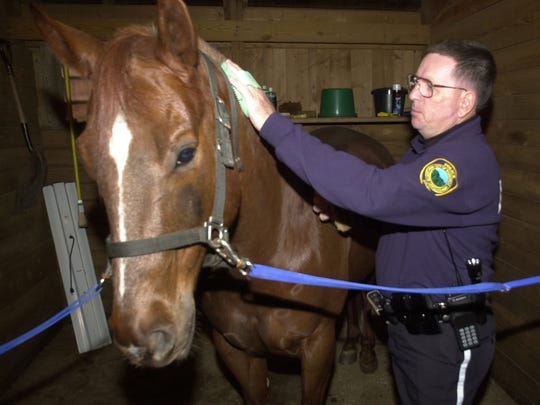 """In this file photo from 20001, """"Gus,"""" the Asheville Police Department's patrol horse stands by officer Paul Reneau."""