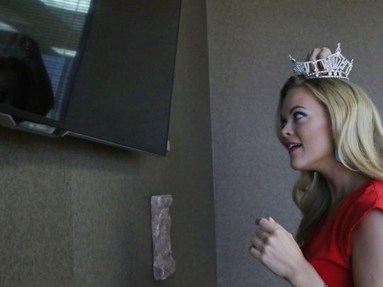Miss Louisiana 2015 April Nelson looks at her reflection in a flatscreen television as she pins her crown on her head on June 10.