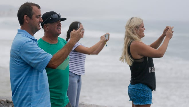 People take photos of the sea in Los Cabos, Mexico, Sunday, Sept. 14, 2014. Hurricane Odile grew into a major storm Sunday and took aim at the resort area of Los Cabos, prompting Mexican authorities to evacuate vulnerable coastal areas and prepare shelters for up to 30,000 people. (AP Photo/Victor R. Caivano)