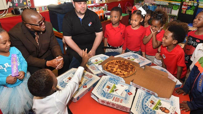 Students at Northeast Elementary receive a treat from Alderman Tyrone Glover when he partnered with Dominos for a student pizza party Friday. See more photos on the Daily World Facebook site. Also pictured is Dominos manager James Shannon.