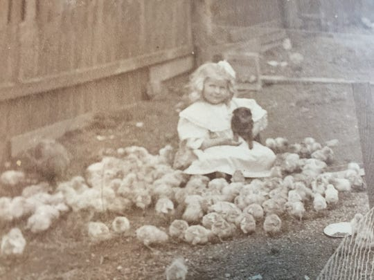 One of the photos shows a young girl sitting in a chicken pen, holding a puppy and surrounded by baby chicks.