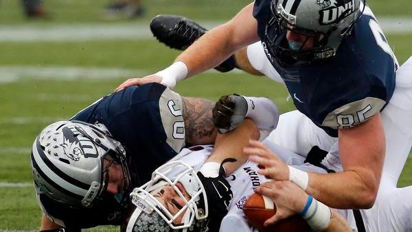 Fordham's Mike Nebrich gets sacked by New Hampshire's Cody Muller, left, and Brian Ciccone during a second-round FCS playoff game, Saturday, Dec. 6, 2014, in Durham, New Hampshire.