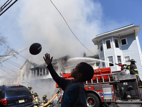 An unidentified child plays with a football at the scene of a four-alarm fire at a residential building on Rose Street in Paterson.