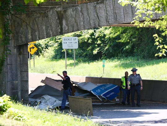 Police officers look at parts of a truck that came