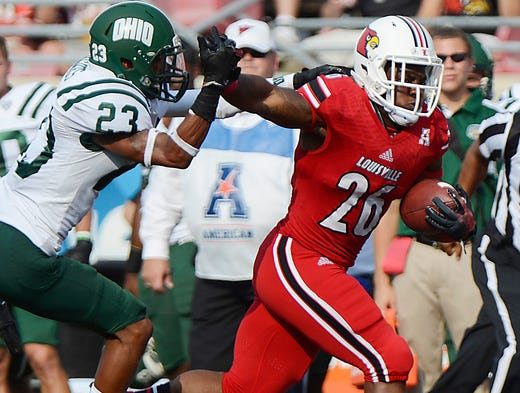 Louisville Cardinals running back Michael Dyer breaks free from Ohio Bobcats safety Xavier Hughes to score a touchdown during at Papa John's Cardinal Stadium.