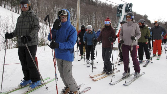 Skiers stand in a lift line Friday at Mad River Glen in Fayston.