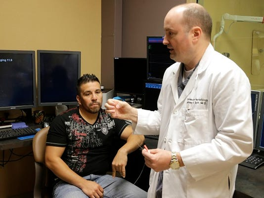 Juan Soriano 37, looks on as Interventional Nerologist james K. Tatum describes the procedure he performed on him during a stroke he suffered which was caused by a Middle Cerebral Artery (MCA) blockage.