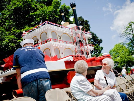 """Janet Currens, right, and Nettie Elliott, center, watch as Corey Miller, left, helps carry the ISS Harmony Belle to its starting position before the fourth annual Cardboard Boat Regatta at Cross Keys Village in 2013 near New Oxford. Ahead of the race, Miller was unsure of the craft's pond-worthiness. """"If we go down, we'll go down in style,"""" Miller said. While it didn't sink, the Harmony Belle came in last in its heat but was awarded a prize for best looking boat."""