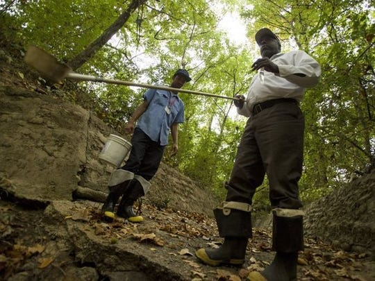 October 2, 2014 - Memphis and Shelby County Health Department employees Torrian Fasom (left) and McKinley Wallace take samples of standing water to check for mosquito larvae. (Brandon Dill/Special to The Commercial Appeal)