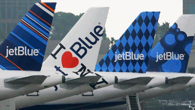 JetBlue planes, each with distinctive tail art, are seen at the JetBlue terminal at Long Beach Airport in Long Beach, Calif., Tuesday, Oct. 25, 2011.