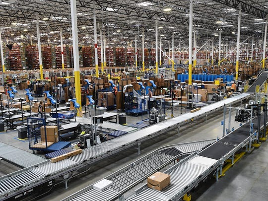Workers are seen with merchandise at Amazon's distribution center in Reno on April 23, 2015.