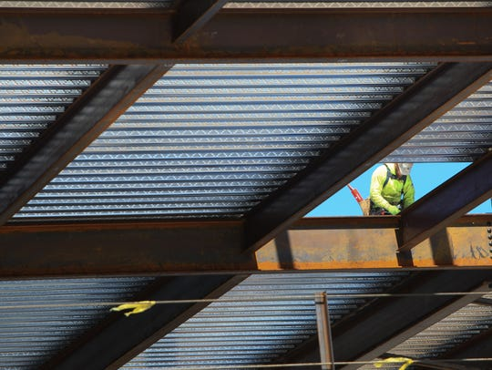 A construction worker works on the third floor of Corporation