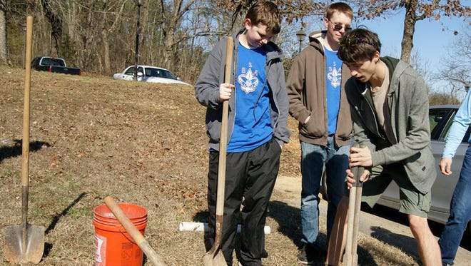 Michael McComas and his fellow Boy Scouts dig a hole for the concrete base of the flag pole at the Fairview Library.