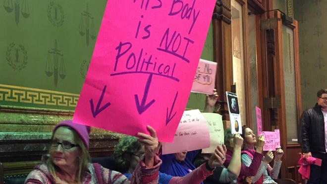 Pro-choice advocates hold signs at a committee hearing March 29.