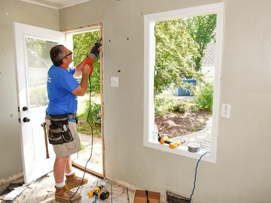 Ross Potts cuts a door and frame loose to recycle as