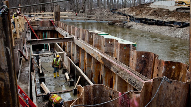 Workers build a replacement bridge Tuesday to carry Gratiot Road over the Pine River in St. Clair Township.