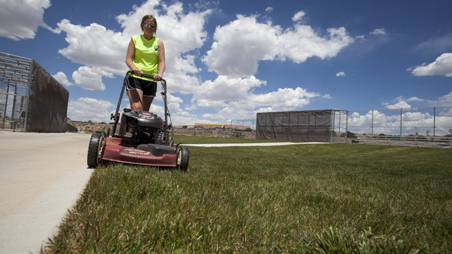 Tael Palmer, landscaper for the Cedar City Parks and Recreation Department, works in the heat of the day to maintain the lawns at the Aquatic Center in Cedar City.