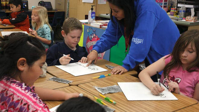 Dixie Sun Elementary School teacher Maria DeWitt helps some of her students out as they work on counting money in her Spanish speaking dual immersion class Friday, Jan. 30, 2015. A new amendment could potentially bring in more funding to schools if it receives a majority vote in the Nov. 2016 elections.
