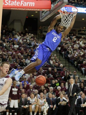 Kentucky's Aaron Harrison (2) dunks past Texas A&M's Peyton Allen during the first half of an NCAA college basketball game Saturday, Jan. 10, 2015, in College Station, Texas. (AP Photo/Patric Schneider)