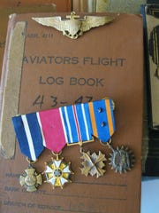 Frederick 'Fritz' Payne's flight logs, pilot wings and medals, including the Navy Cross (far left).