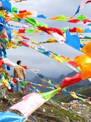 Buddhist prayer flags flutter in the wind atop a 14,000-foot pass in Tibet.
