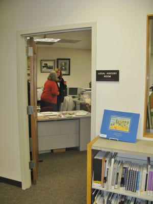 Penfield Town Historian, Kathy Kanauer (in red sweater) is showntalking to a visitor at the Local History Room Open House. Visitors with memories of early kitchen equipment were invited to speak about what it was like to make dinner before microwave ovens, garbage disposers, dishwashersand automatic ice makers in the refrigerator.