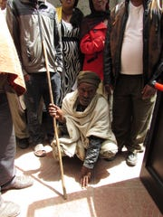 A polio victim arrives for a checkup during a Rotary
