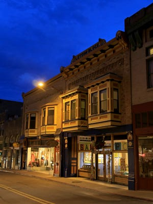 The SAM•POE Gallery and other Old Town businesses glow in the twilight along Tombstone Canyon Road in Bisbee, Arizona.