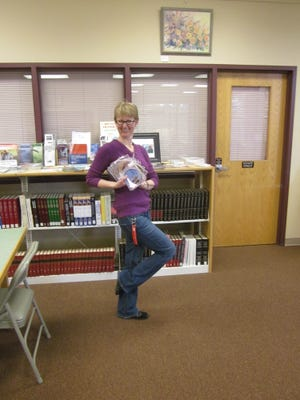 Ruidoso Library Assistant Trish Koenig strikes a dance pose as she displays a fan of dance DVD's donated by the Ruidoso dance community that meets at the Ruidoso Community Center on Mondays and Wednesdays. The DVD's are available for checkout by any library card holder.